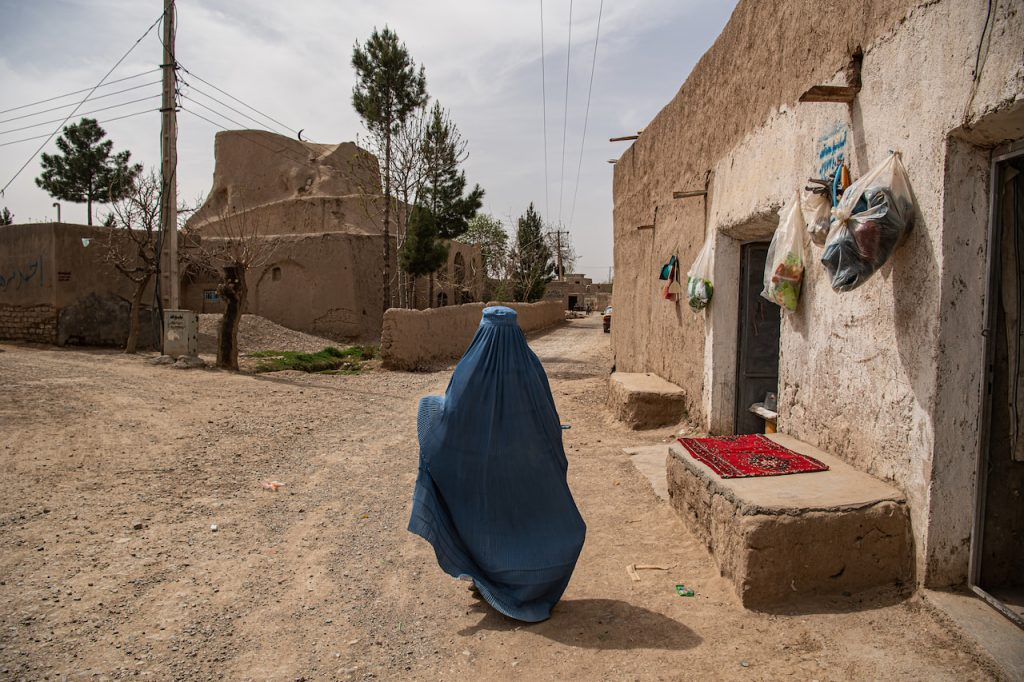 Afghan woman beside old house